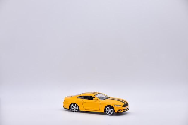 白い背景の上の黄色いおもちゃの車、黄色い車のクローズアップ