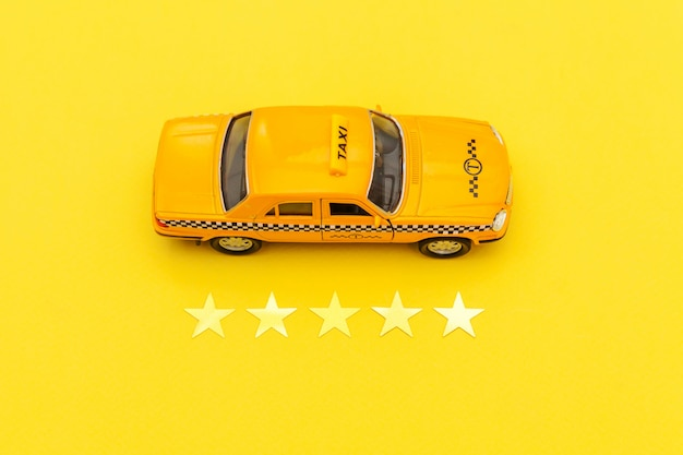Yellow toy car taxi cab and 5 stars rating isolated on yellow background. phone application of taxi service for online searching calling and booking cab concept. taxi symbol. copy space.