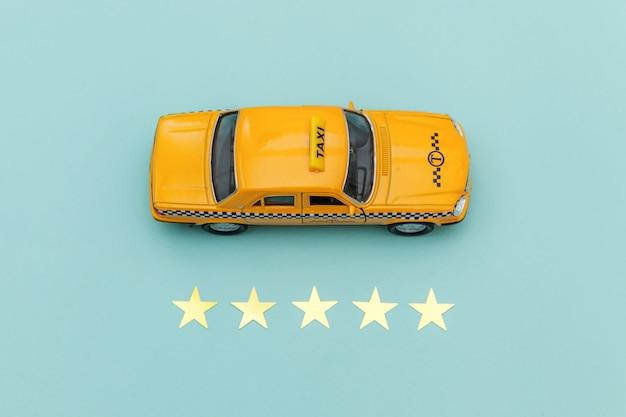 Желтая игрушка автомобиль такси и рейтинг 5 звезд, изолированные на синем фоне.