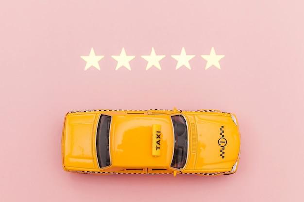 Желтый игрушечный автомобиль такси и рейтинг 5 звезд, изолированные на розовом фоне.