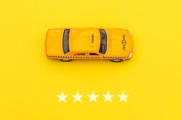 Желтый игрушечный автомобиль такси и рейтинг 5 звезд, изолированные на желтом фоне.