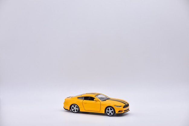 Yellow toy car on white background, yellow car closeup