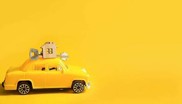 색상 배경에 지붕에 집 열쇠가 있는 노란색 장난감 자동차. 새 집으로 이사, 모기지, 아파트 구입, 택시. 공간을 복사합니다.