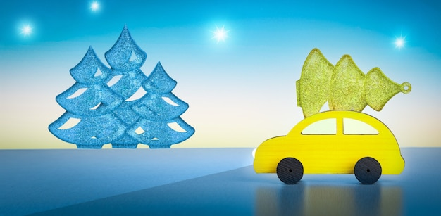 Yellow toy car with a christmas tree on the roof on night sky background. new year concept. banner.