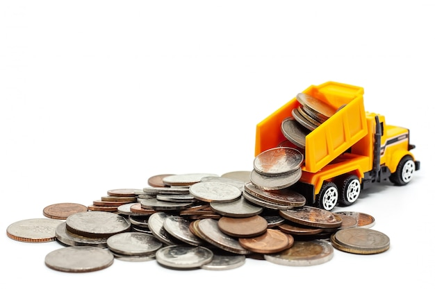 A yellow toy dump truck with pile of coins on white