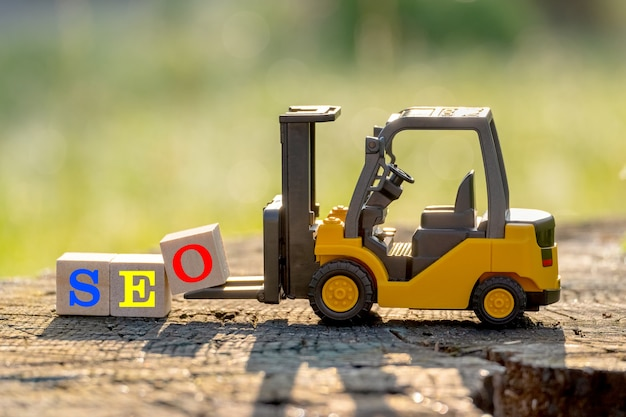 노란색 장난감 지게차는 나무 테이블에 단어 seo (검색 엔진 최적화의 약어)를 완료하기 위해 문자 블록 o를 보유합니다.
