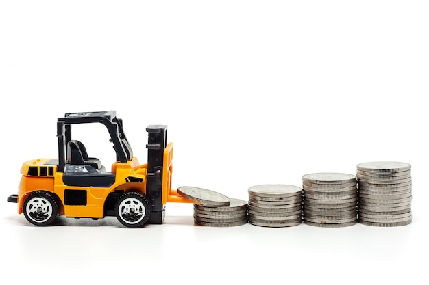 A yellow toy forklift with pile of coins on white
