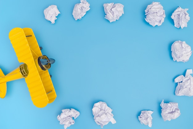 Yellow toy plane on blue background with paper cloud