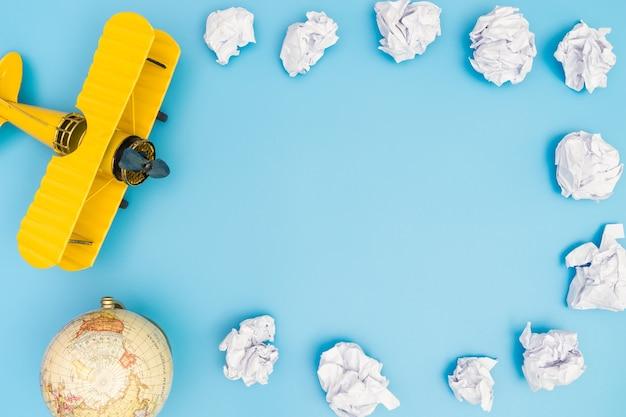 黄色のおもちゃ飛行機は、紙の雲にブルー額装コピースペース
