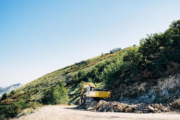 黄色の追跡されたトラクターは、山の背面図の近くに石を掘削します
