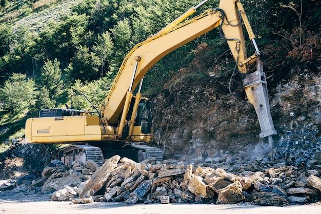 黄色の追跡されたトラクターが山の近くで石を掘削します