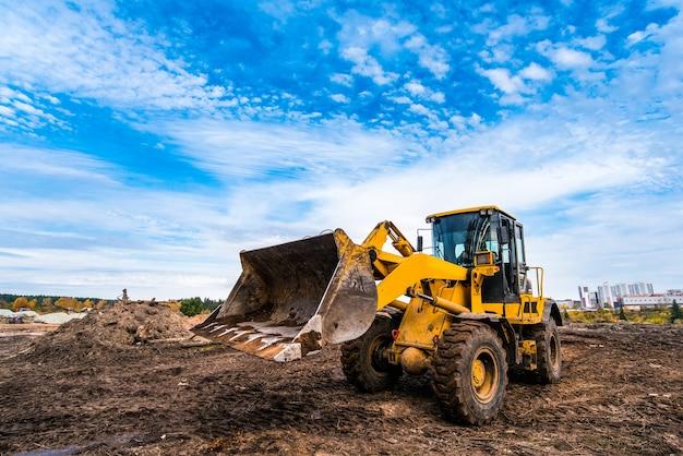 Желтый трактор выравнивает землю у нового строящегося дома