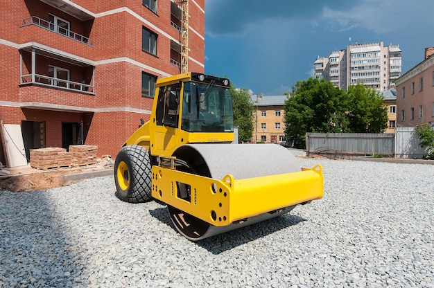 Желтый тракторный каток уплотняет камни