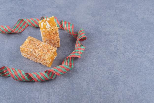 Delizia turca tradizionale gialla con arachidi su sfondo grigio.