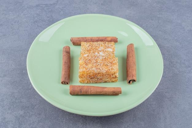 緑のプレートにピーナッツと黄色の伝統的なトルコ菓子