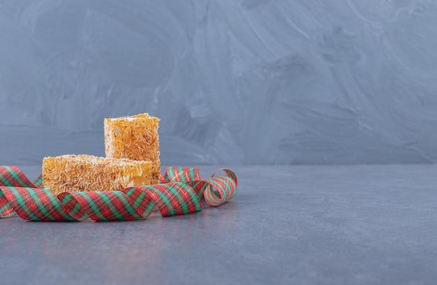 灰色の背景にピーナッツと黄色の伝統的なトルコ菓子。