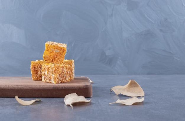 木の板にピーナッツを添えた黄色の伝統的なトルコ菓子。