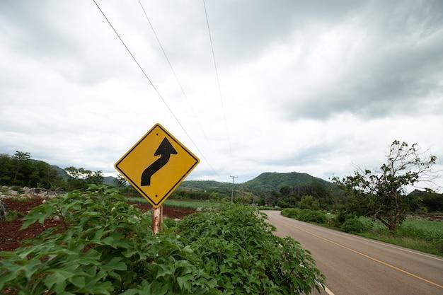 Желтые дорожные знаки, предупреждающие об извилистой дороге впереди на зеленой траве на заднем плане