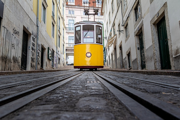 Yellow tram going down a narrow alley surrounded by old buildings