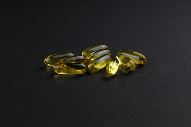 Yellow transparent capsules with fish oil on a black background
