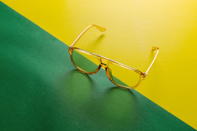 Yellow transparent sunglasses frame on anstract green diagonal background