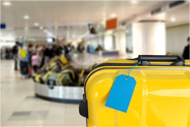 파란색 태그가 있는 노란색 여행용 케이스. 여행 컨셉