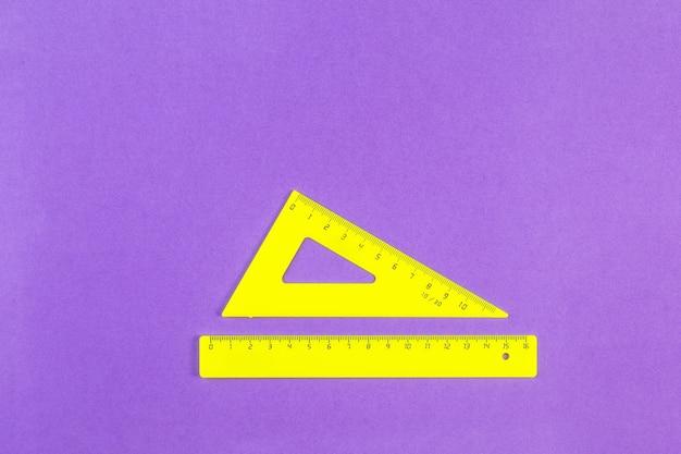 Желтый треугольник и линейка на фиолетовой поверхности