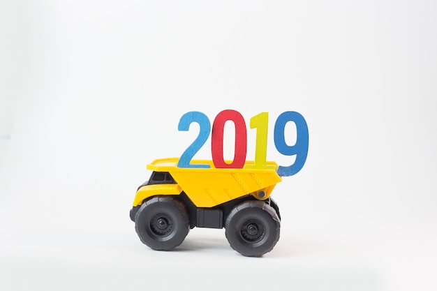 The yellow truck hold 2019 number on white background.
