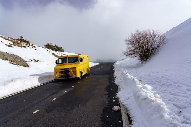 눈에 노란색 트럭 덮여 높은 산악 도로. la morcuera.