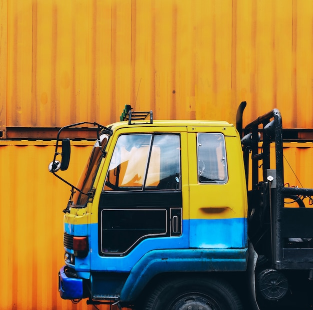 Желтый грузовик, припаркованный возле желтой контейнерной коробки