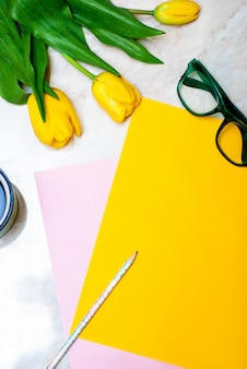 Yellow tulip, coffee, green glasses and colorful paper on marble background