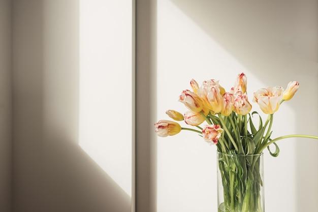 흰 벽에 유리 꽃병에 노란 튤립 꽃 꽃다발
