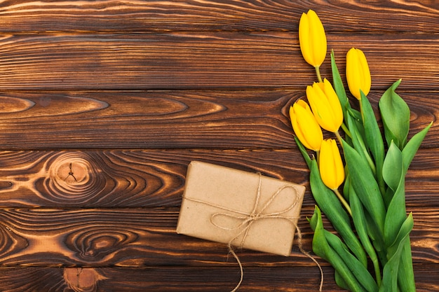 Yellow tulip flowers with gift on table
