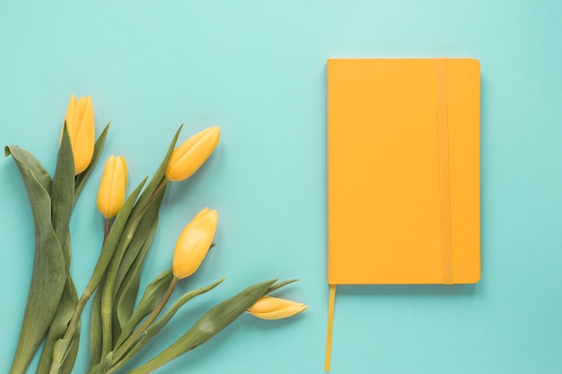 Yellow tulip flowers with notebook on table