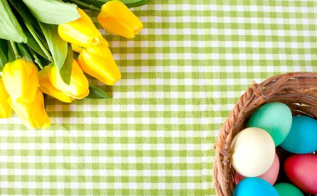 노란 튤립과 초라한 체크 무늬 녹색 식탁보 위에 다채로운 계란 바구니. 평면도. 공간을 복사하십시오.