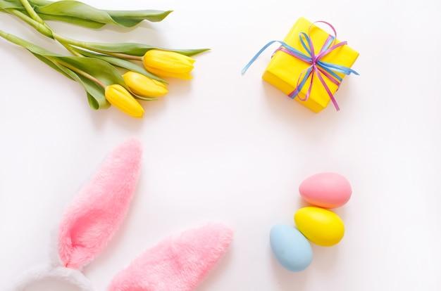 Желтые тюльпаны и красочная подарочная коробка пасхальных яиц, кроличьи уши на белом фоне, вид сверху.