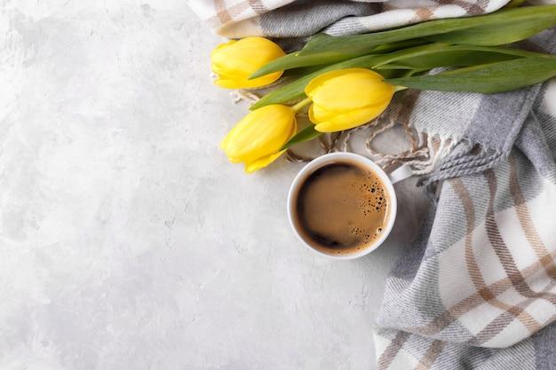 Желтые тюльпаны и чашка кофе Premium Фотографии