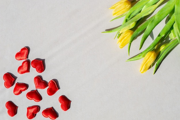 Желтые тюльпаны и красные сердца на сером фоне плоской планировки шаблона для поздравлений для женщин