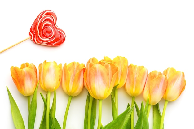 Желтые тюльпаны и красный леденец на палочке на белом изолированном фоне. весной и летом фон. день матери, пасха и сезонный праздник