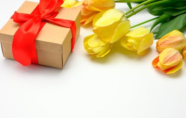 白い表面に赤いリボンで結ばれた黄色いチューリップと四角い箱、母の日、誕生日のお祝いの表面