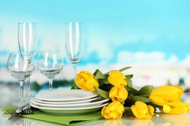 青い自然の背景で提供するための黄色のチューリップと道具