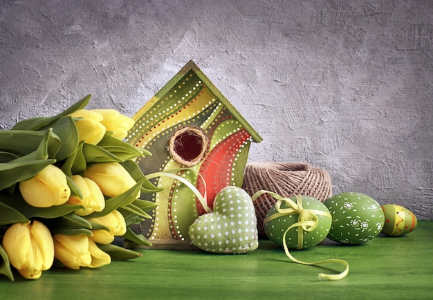 Yellow tulips, birdhouse and painted easter eggs with stuffed heart, spring decorations