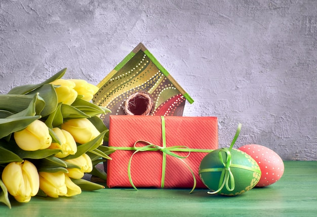 Yellow tulips, birdhouse and painted easter eggs with wrapped present