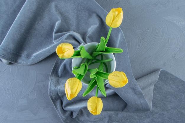 Tulipani gialli in un secchio su un pezzo di tessuto, sullo sfondo bianco.