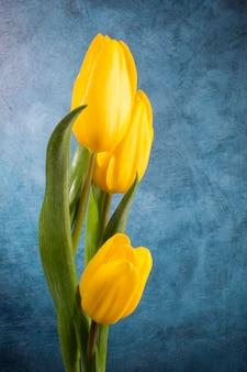 Букет желтых тюльпанов на синем фоне гранж