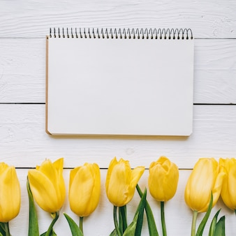 Yellow tulips bunch on white wooden planks rustic barn rural table background. empty space for lettering, text, letters, inscription. beautiful square flat lay postcard template.