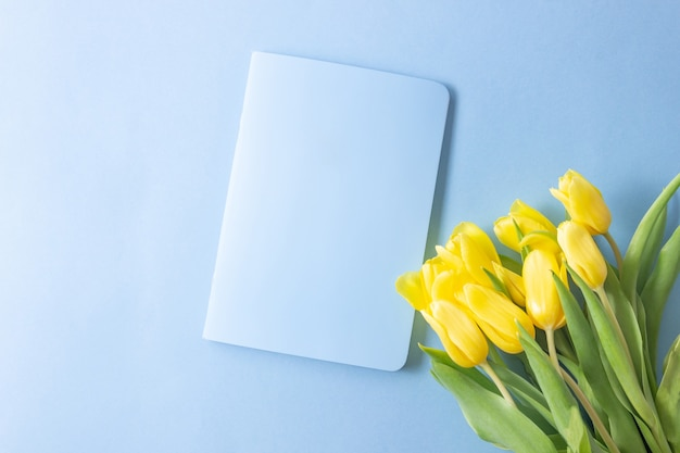 Yellow tulips flowers on blue background with an open notepad for writing. mother's day, birthday, valentine's day. concept of holiday. symbol of spring. flat lay, top view, copy space