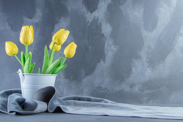 흰색 바탕에 직물 조각에 양동이에 노란색 튤립. 고품질 사진