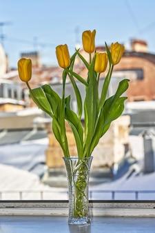 Желтые тюльпаны в хрустальной вазе на подоконнике