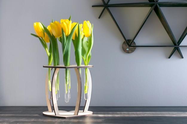Желтые тюльпаны в деревянной вазе на столе. копировать пространство